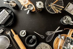 Kitchen utensils (cooking tools) on black chalkboard background. Kitchenware collection captured from above (top view, flat lay). Layout with free copy (text) space.