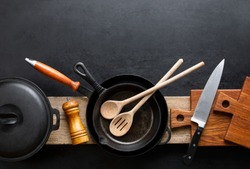 Kitchen utensils dark background with cast iron black kitchenware, top down view, blank space for a text
