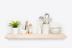 Kitchen utensils, flower pot and dishware on natural wooden shelf
