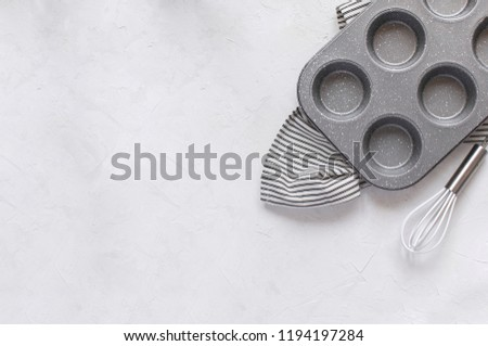 Kitchen utensils for baking - Cupcake metal mold Whisk on Crumpled Striped Napkin. Top view, Flat lay, Copy space. Minimal picture.