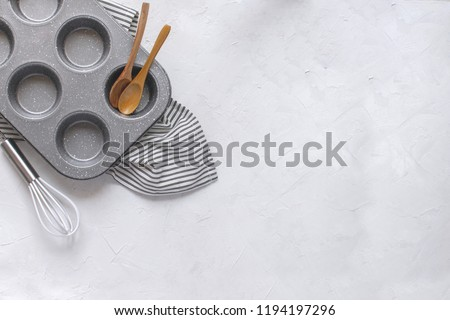 Kitchen utensils for baking - Cupcake metal mold, Whisk, wooden spoons on Crumpled Striped Napkin. Top view, Flat lay, Copy space. Minimal picture.