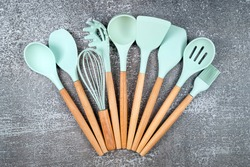 Kitchen utensils, home kitchen tools, mint rubber accessories on dark background. Restaurant, cooking, culinary, kitchen theme. Silicone spatulas and brushes