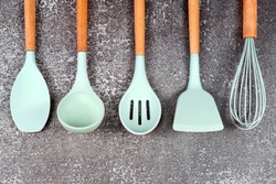 Kitchen utensils, home kitchen tools, mint rubber accessories on dark background. Restaurant, cooking, culinary, kitchen theme. Silicone spatulas and brushes, free copyspace for text