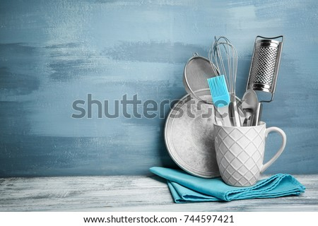 Kitchen utensils in cup on table against wall stock photo