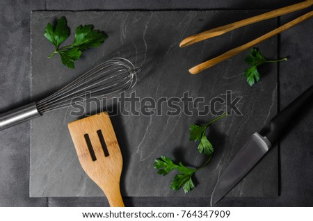Kitchen utensils layout with fresh green parsley leaves on dark grey stone background. Can be used for advertising, menus, brochures, food blogs. Studio lighting #764347909