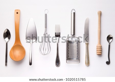 Kitchen utensils, metal and wooden, isolated on white background. Spoons, fork, knife, honey spoon, grinder, whisker. Top view - Shutterstock ID 1020515785