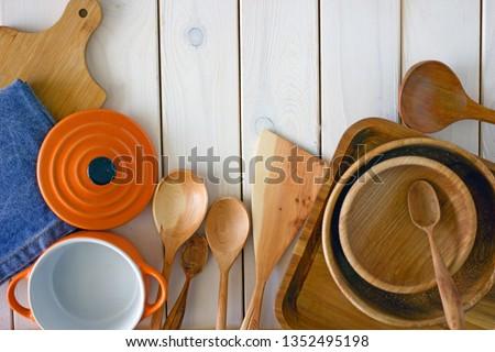 Kitchen utensils on wooden background. Kitchen utensils over wood background wooden table with copy space.Various wooden kitchen utensils on table top view with copy space. Culinary Background.  #1352495198