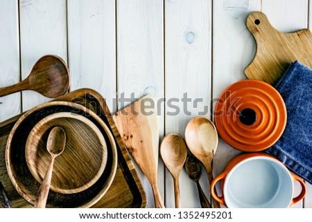 Kitchen utensils on wooden background. Kitchen utensils over wood background wooden table with copy space.Various wooden kitchen utensils on table top view with copy space. Culinary Background.  #1352495201