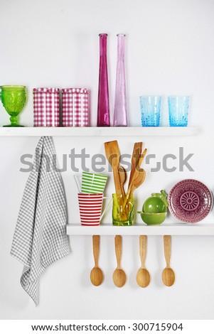 Kitchen utensils on wooden shelves, close up