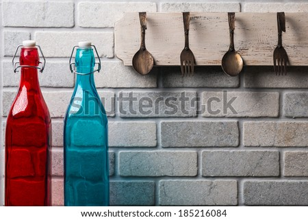 Kitchen wall with spoons and forks and colored bottles/Kitchen lifestyle brick wall/ Kitchen brick wall with colorful bottles