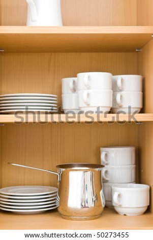 Kitchen-ware in top closet on wooden shelves.