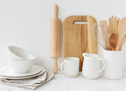 Kitchen white tableware wooden utensils on the table. Eco friendly kitchen concept. Minimalism kitchen scandinavian style. Copy space fot text