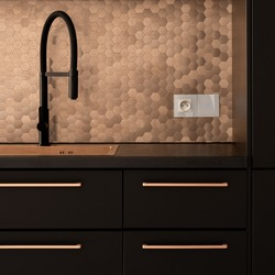 Kitchen with black faucet, drawers and cupboards and with golden handles, sink, hexagonal wall tiles