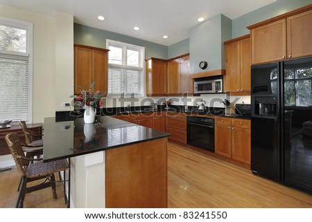 Kitchen with breakfast bar and wood cabinetry - stock photo