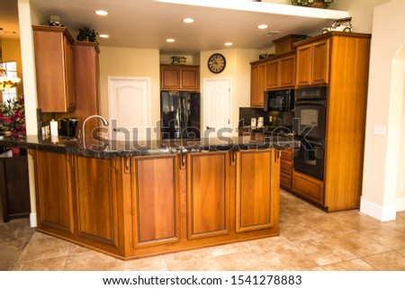 Kitchen With Granite Counters & Rich Wood Grain Cabinets