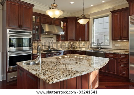 Kitchen With Granite Island And Cherry Wood Cabinetry Stock Photo