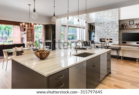 Kitchen with Island, Sink, Cabinets, and Hardwood Floors in New Luxury Home, with View of Living Room, Dining Room, and Outdoor Patio