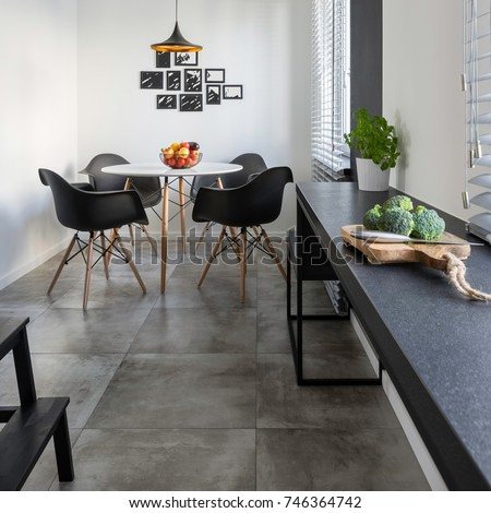 Kitchen with long, granite countertop, concrete floor tiles and round table and chairs #746364742