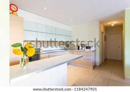 Kitchen with peninsula and yellow flowers. Nobody inside