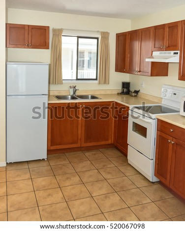 Kitchen with wooden cabinets, fridge, and electric stove