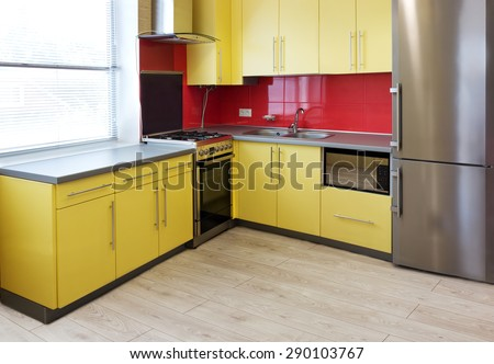 kitchen with yellow cupboards, topped with a grey worktops and fitted with appliances including refrigerator, microwave, oven, extractor hood, a wall with a red tile and floor with soft grey laminate