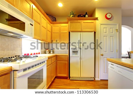 Kitchen with yellow wood cabinets and white appliances and hardwood floors.