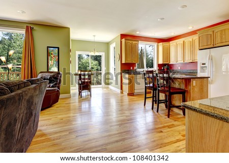 Kitchen with yellow wood floor and green wall near living room.
