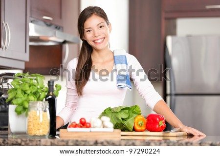 kitchen woman making healthy food standing happy smiling in kitchen preparing salad. Beautiful cheerful multicultural Chinese Asian / Caucasian young woman at home. - stock photo