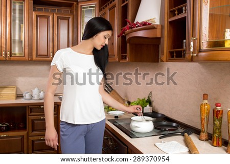Kitchen Woman. Young beautiful girl holding a frying pan.  Kitchen background