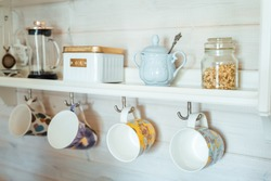 Kitchen wooden shelf with tea leaves in gold box and accessories, blue sugar bowl with spoon, strainer, press. Many colorful cups, mugs are hanging from hooks. Cozy interior in a country house.