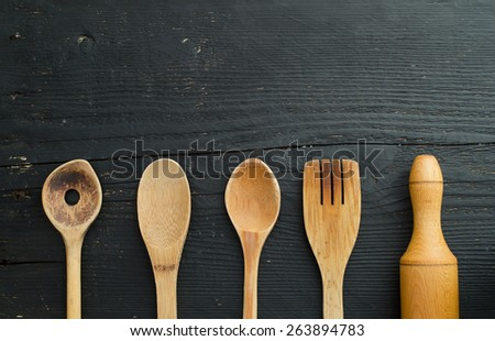 Kitchen wooden utensils over black wooden table. Horizontal and above view with copy space for text or other design