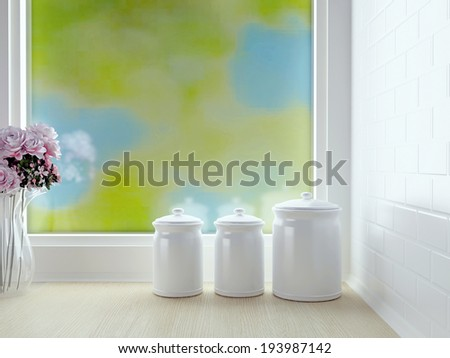 Kitchen worktop with containers and flowers in front of window. White kitchen design.