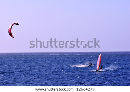 kite boarder and wind surfer on parallel tacks toward camera on caribbean blue water