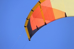 Kite boarders kite flying in the air. The kite is orange, yellow and black. Blue sky background