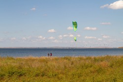 Kite parachutes are visible over the lake, a plain with orange grass.