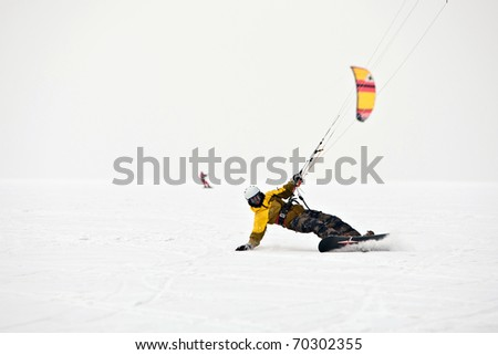 Kite surfer on snowboard in the snow