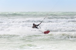 Kite surfer rides among the waves of North sea, France