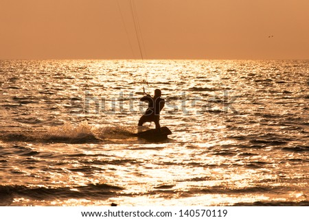 Kite surfer sailing in the sunset sea