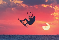 Kite-surfing at beautiful sunset.Kite surfer (silhouette) in flight over the Mediterranean Sea.Sports and Recreation in the Mediterranean.Holidays on nature.Seasons.Vacation theme.Toned colors image