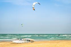 Kite surfing in desert windy beach with windsurf board - Exlcusive adventures in tropical destinations worldwide