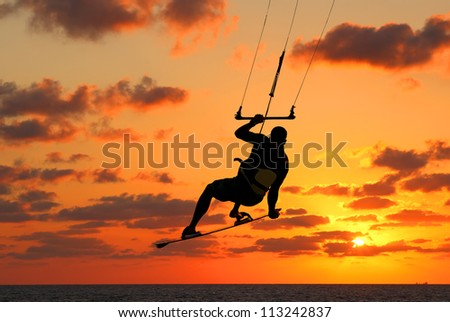 Kite-surfing on orange sunset's background - stock photo