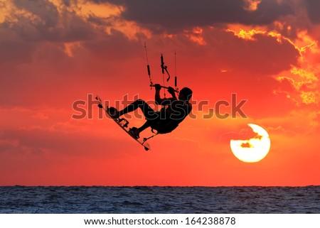 Kite-surfing on orange sunset's background