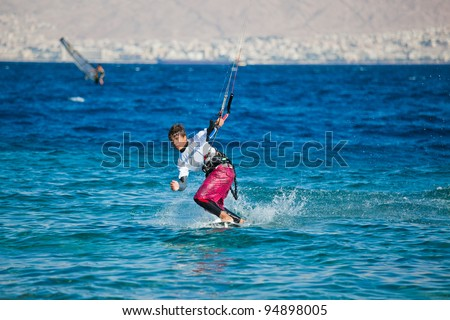 Kite surfing on the sea. The beautiful suntanned young guy goes for a drive on a board by the sea
