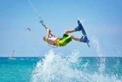 kiteboarder athlete kitesurfing and performing jumping tricks
