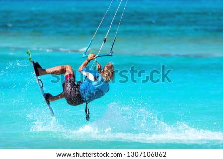 Photo of  Kiteboarder kitesurfer athlete performing kitesurfing kiteboarding tricks unhoocked