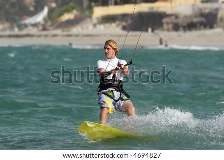 Kiteboarder riding in the ocean on a sunny day near the beach