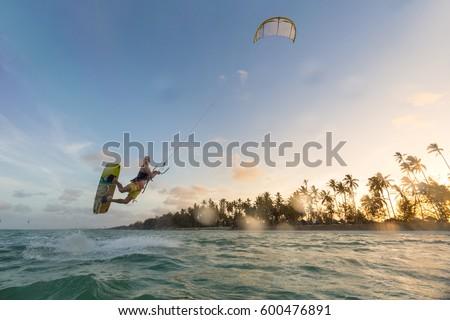 Kiteboarding. Fun in the ocean. Extreme Sport Kitesurfing. Kitesurfer jumping high in the air during dusk moonlight lit session.