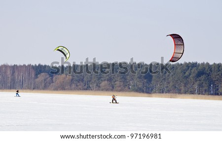 Kiteboarding with snowboards on frozen lake in winter. Active and modern people leisure.