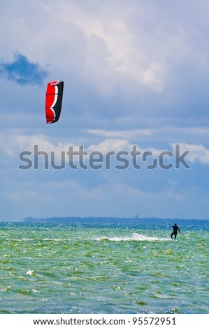 Kiter with red and black kite surfing against blue sky