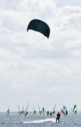 Kitesurfer against many windsurfers